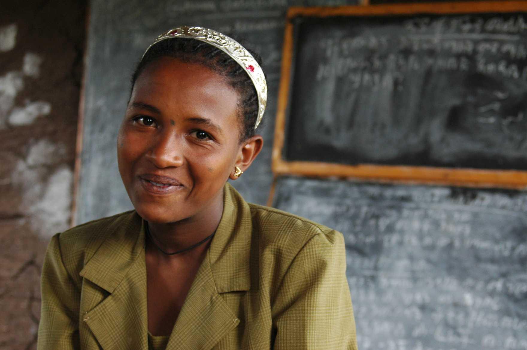 En flicka i grön skjorta sitter framför en svart tavla i ett klassrum.