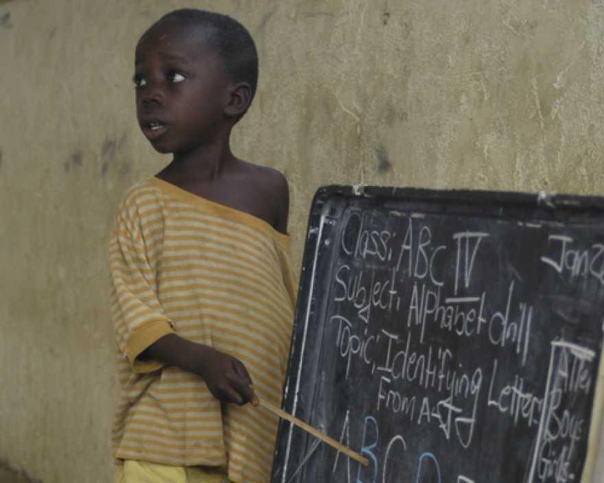 En pojke i gul tröja pekar mot en svart tavla med vit text på. Tavlan är målad på insidan av locket till en stor plåtlåda - school-in-a-box.