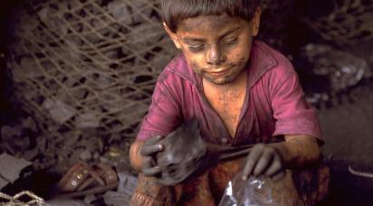 En liten pojke med sotigt ansikte fyller små platspåsar med kol.