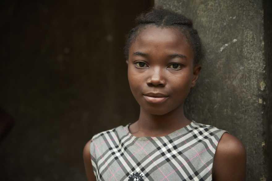 Flicka i Sierra Leone mot en stenvägg. Operation Dagsverke 2022 - ökad kunskap om mens ger fler flickor chansen att stanna i skolan.