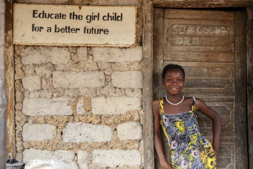 """Flicka i Sierra Leone står bredvid en skylt som säger """"Utbilda flickor för en bättre framtid"""". Operation Dagsverke 2022 - ökad kunskap om mens ska ge fler flickor chans att gå kvar i skolan."""