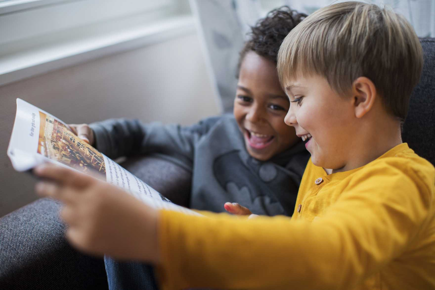 Två barn ler och läser en tidning