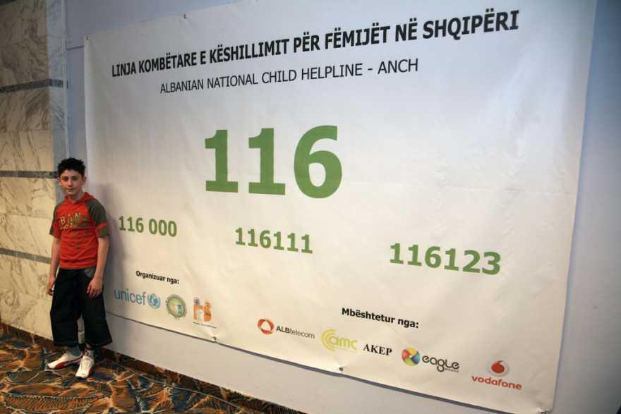 Pojke framför skylt för Barnens hjälptelefon i Albanien.