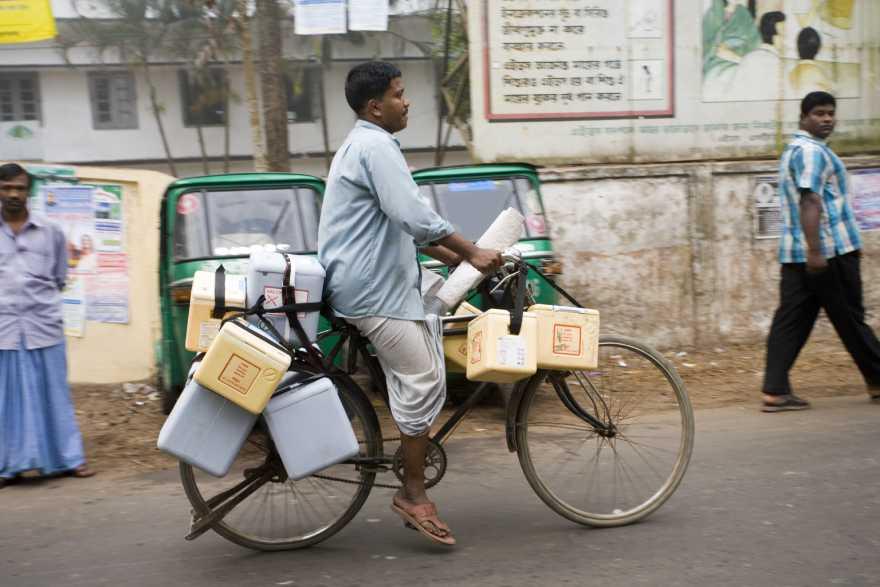 En man cyklar med flera kylväskor fyllda med vaccin på cykeln.
