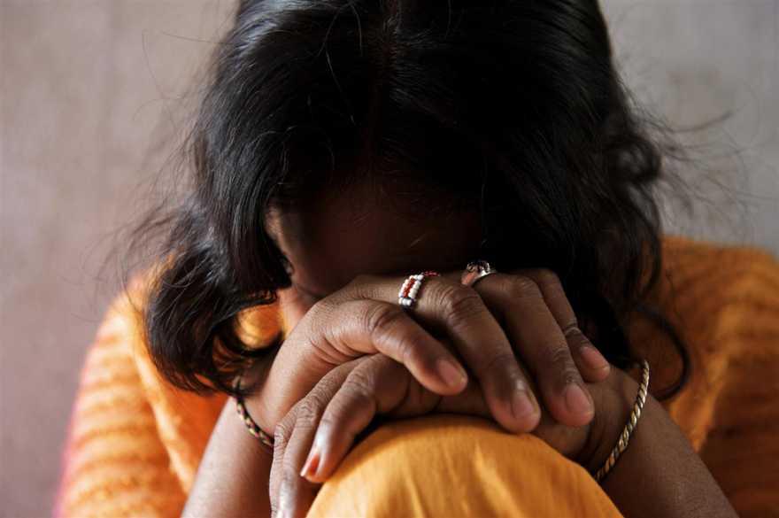En flicka med mörkt hår lutar ansiktet mot knutna händer över sitt knä.