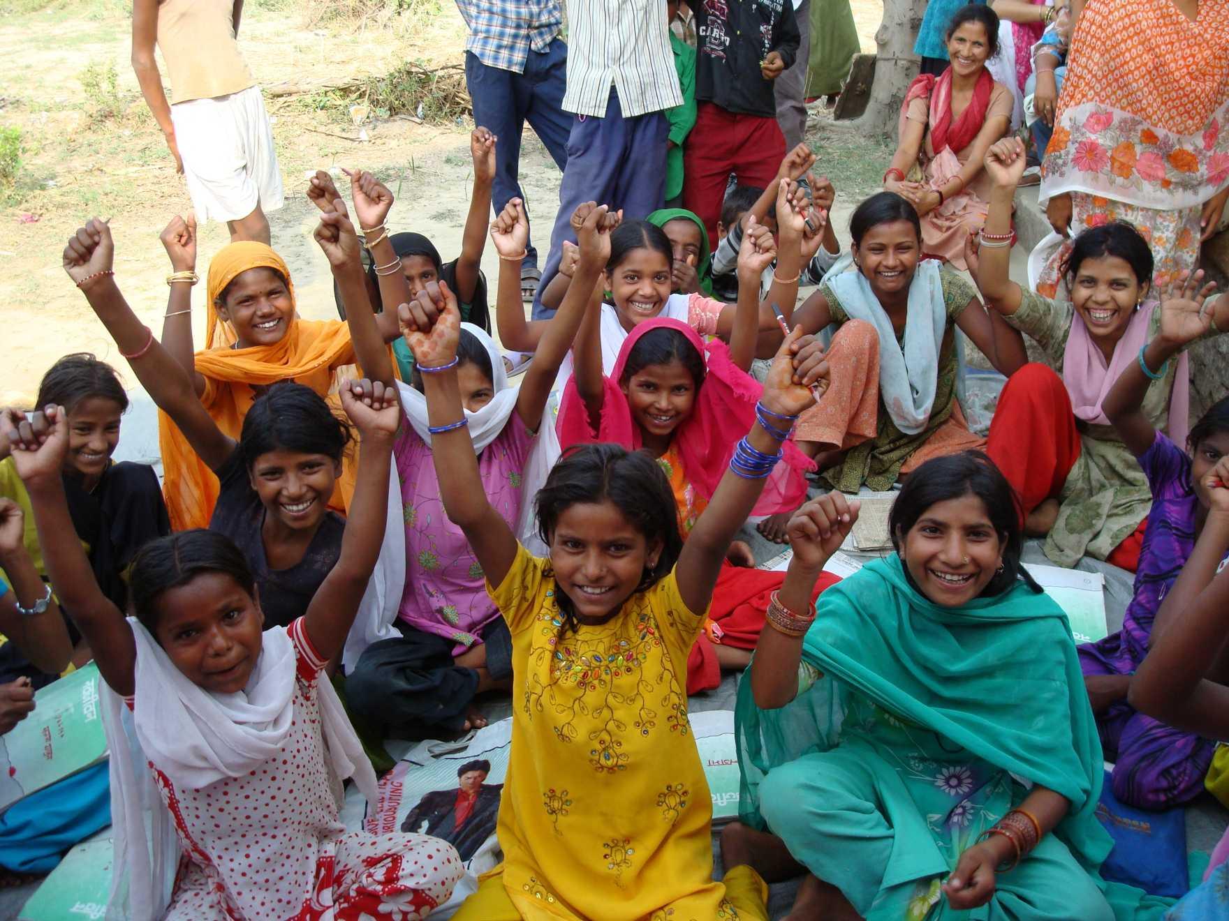 En grupp flickor i färgglada kläder sitter på marken och sträcker upp armarna och ler.