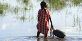 En flicka går med en vattendunk i knähögt vatten.