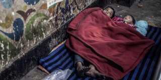 Gatubarn sover på en bussterminal i Dhaka, Bangladesh.