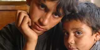 Två pojkar med mörkt hår tittar in i kameran.