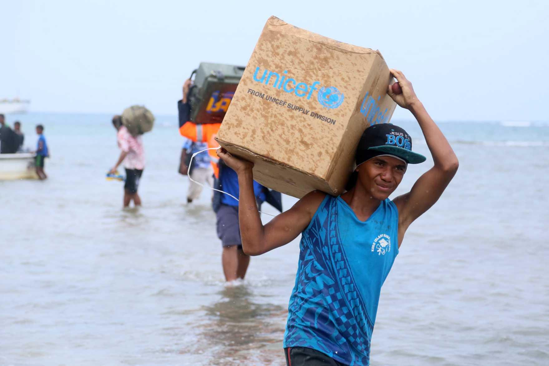 En man går i vatten, in mot stranden, med en UNICEF-kartong på axeln.
