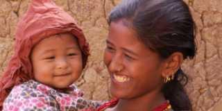 En bebis med en mössa hålls i famnen av sin leende mamma.
