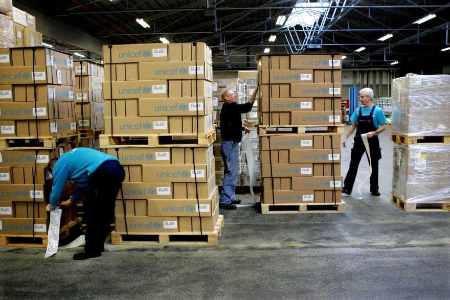 Tre män packar lastpallar fulla med förnödenheter i en stor lagerbyggnad.