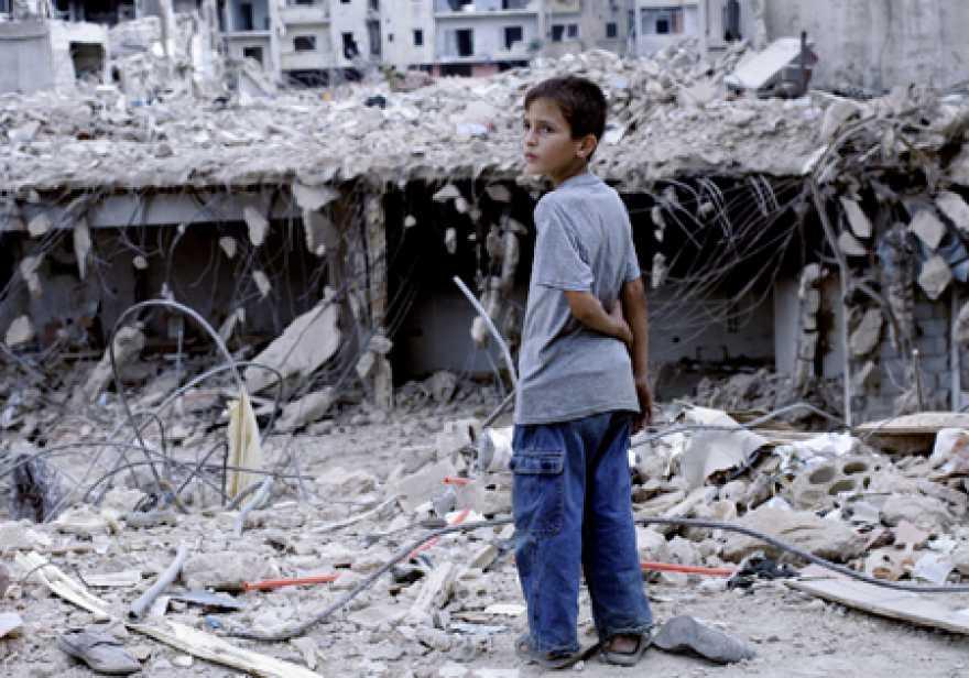 En pojke står framför rasmassor på en gata i Beirut, Libanon.