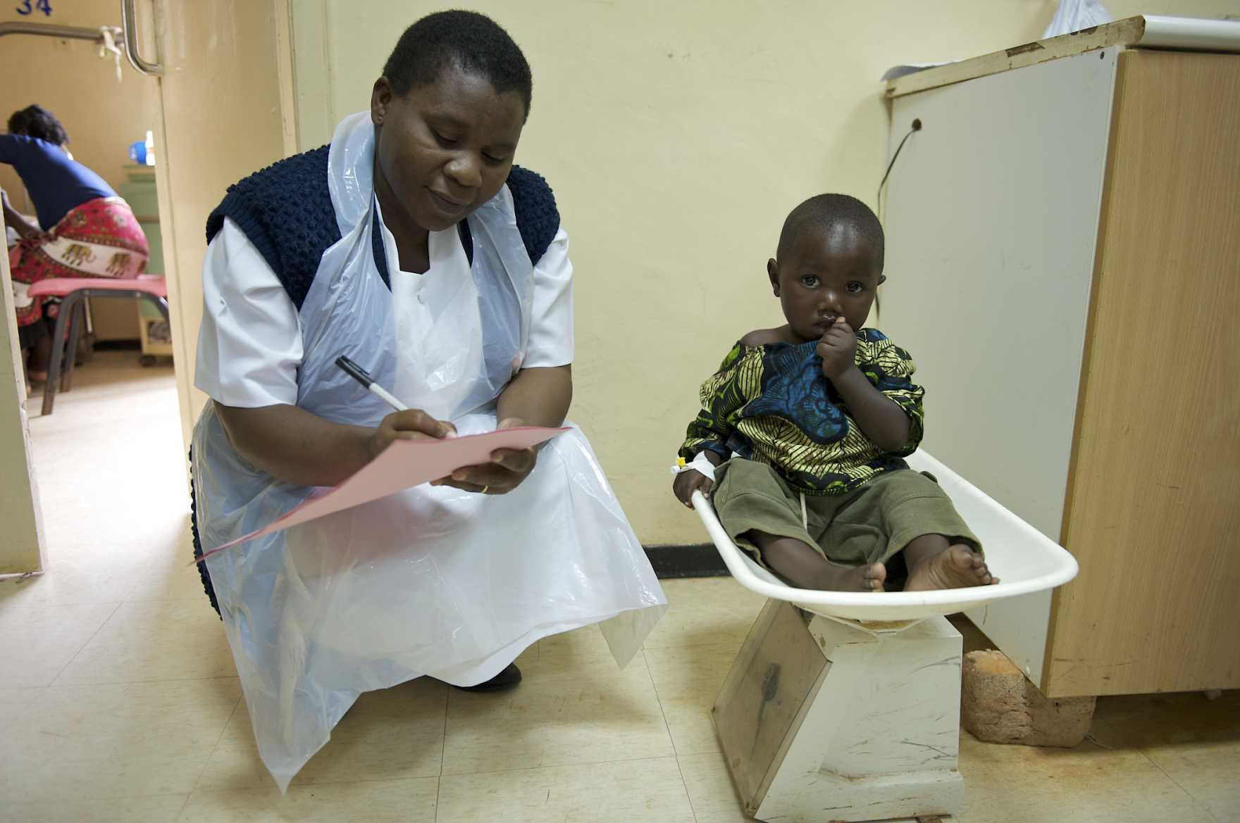 Ett litet barn sitter på en våg, bredvid en sjuksköterska.