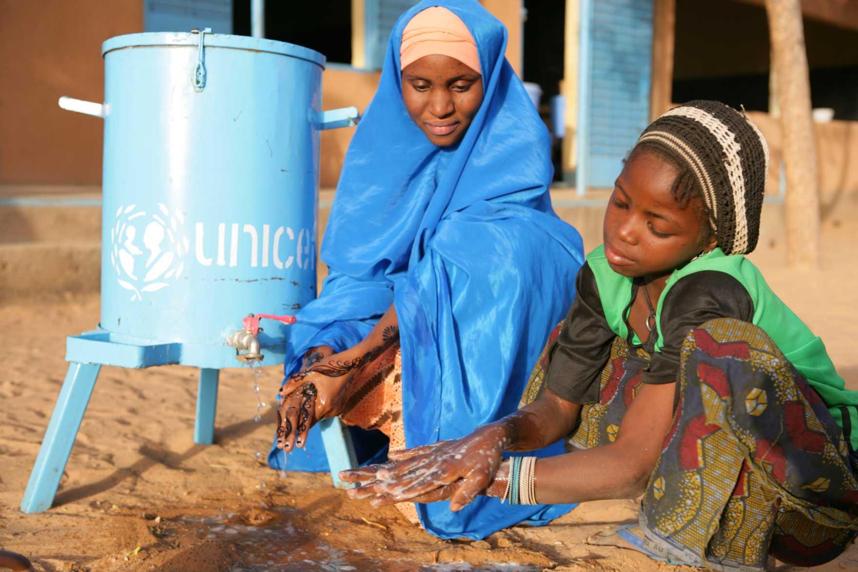 En flicka och hennes lärare tvättar händerna under en kran vid en blå vattenbehållare från UNICEF.