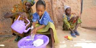 En flicka får hjälp att tvätta händerna då en äldre kvinna häller vatten från en vattenkanna.