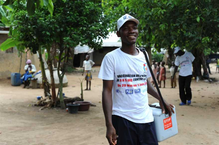 En hälsoarbetare bär på en kylväska med livsviktigt vaccin, i en vaccinationskampanj i Elfenbenskusten.