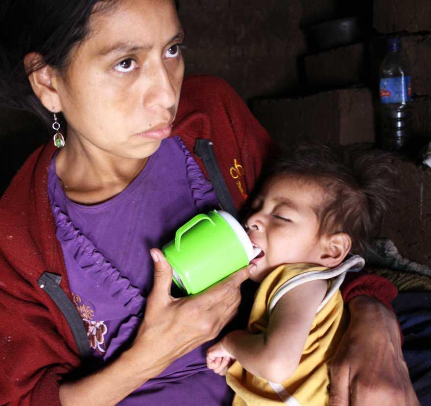 Ett litet barn matas av sin mamma med näringstillskott i en mugg.