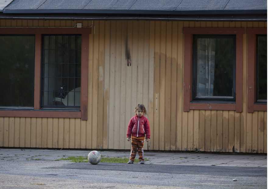 Ett litet barn i röd jacka står framför ett hus med en fotboll på marken bredvid sig.