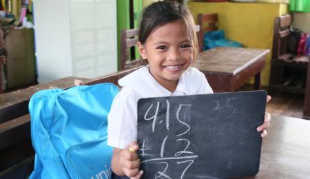 En flicka med mörkt hår och vit tröja ler och håller i en svart tavla med siffror på.