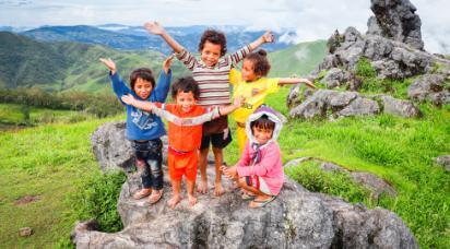 Glada barn står på en sten och brer ut sina armar i Östtimor.