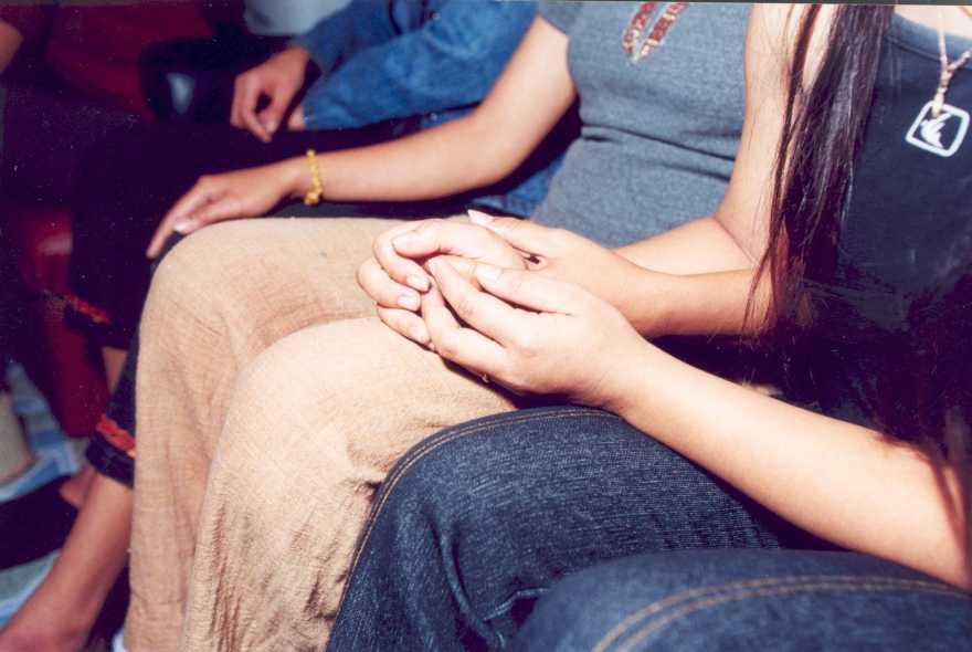 Några flickor sitter bredvid varandra med händerna i knät.