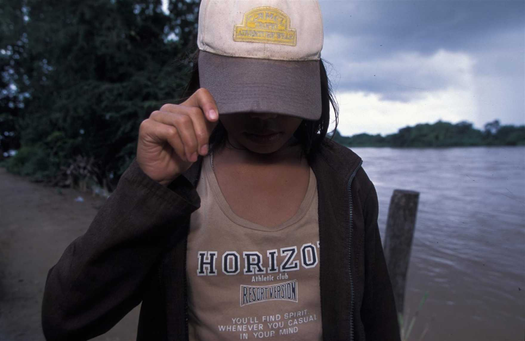 En flicka döljer sitt ansikte under en keps.