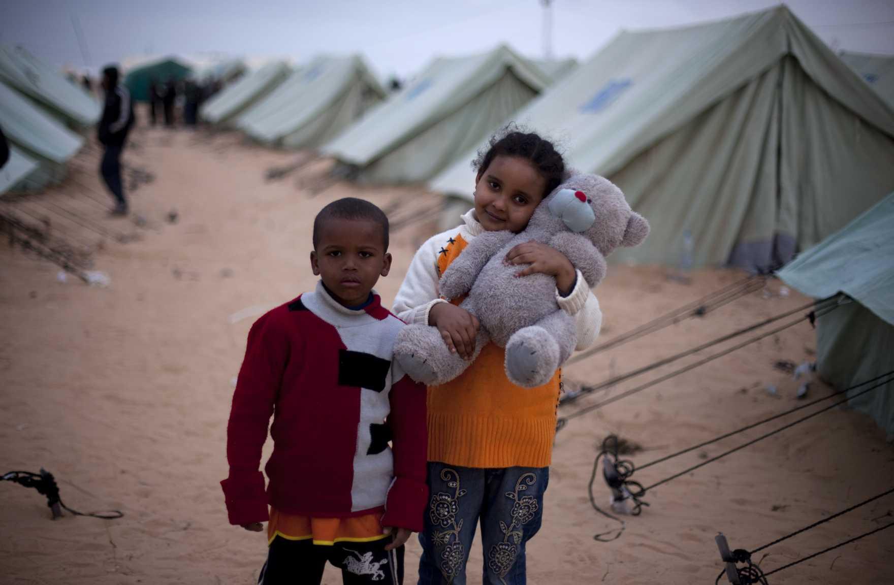Två barn står utanför några tält i ett flyktingläger på gränsen mellan Tunisien och Libyen. En flicka håller en nallebjörn i famnen.