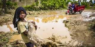 En flicka bär en stock över lerig mark.