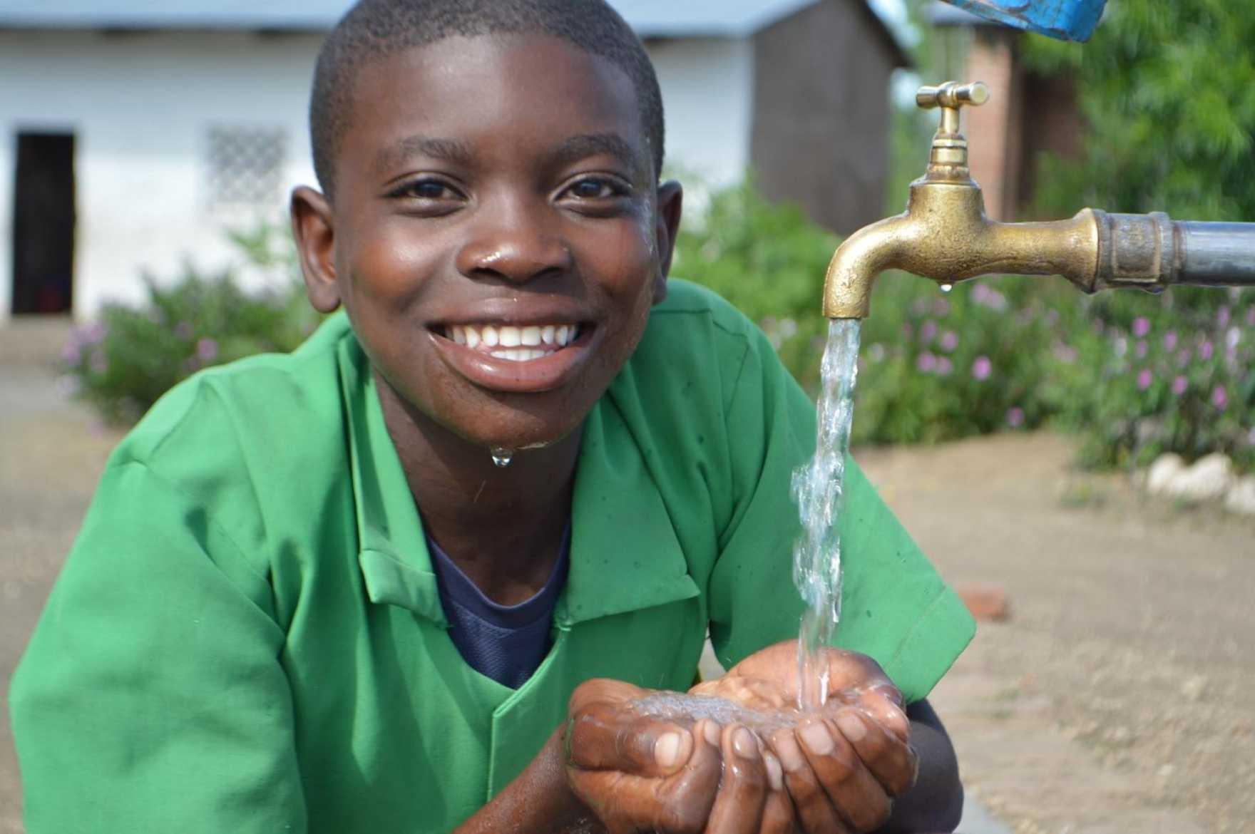 Glad pojke håller händerna under kran med rinnande vatten.