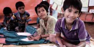 Barn sitter på golvet i klassrum med skolmaterial och ryggsäckar.