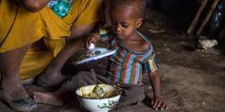 Pojke äter gröt ur en skål.