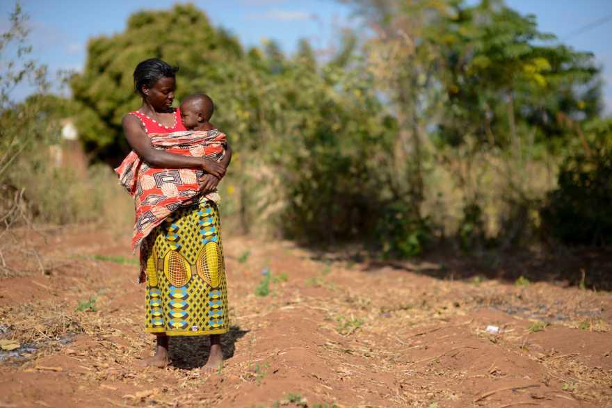 En kvinna med sitt barn i famnen på torr jord.