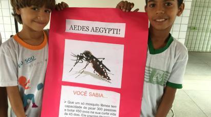Två barn i Brasilien håller upp skylt med information om zikavirus.