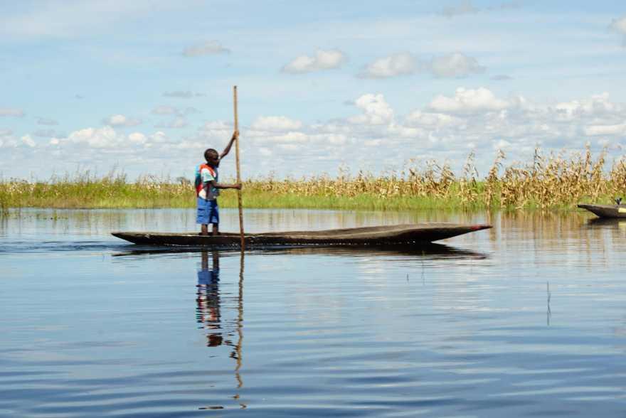 En pojke paddlar stående i en båt.