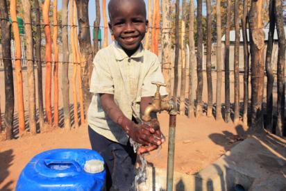 En glad pojke tvättar händerna under en vattenkran.