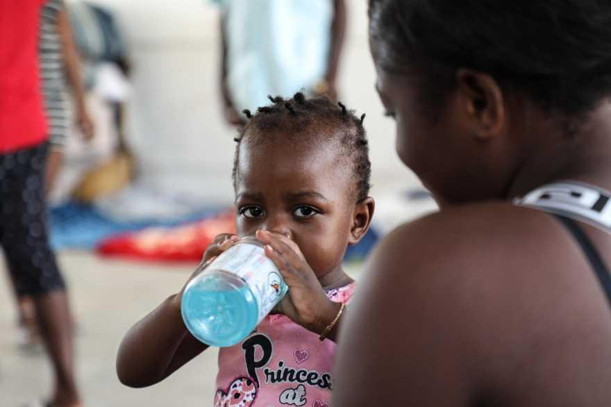 En liten flicka dricker från en vattenflaska.