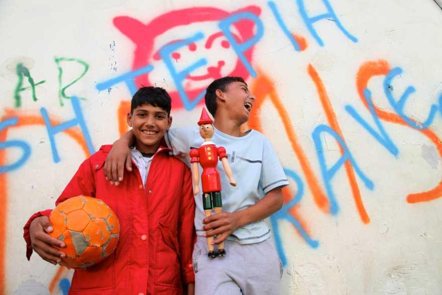 Glada pojkar med boll och leksak i Albanien.