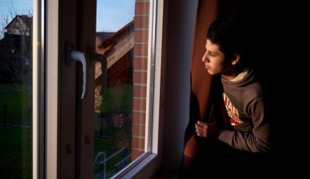 En tonårspojke tittar ut genom ett fönster