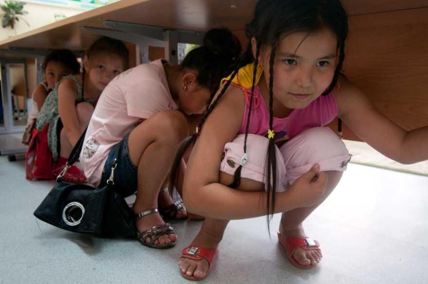 Barn gömmer sig under skolbänkar, Kazakhstan.