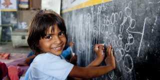 Ett barn i blå tröja ler och ritar på en svart tavla.