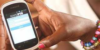 En kvinnas händer håller i en mobiltelefon.