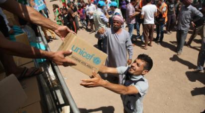 Man tar emot UNICEF-kartong från person på lastbil.