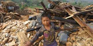 En pojke i Nepal står framför en hög med bråte, rasmassor från det som var hans hem.