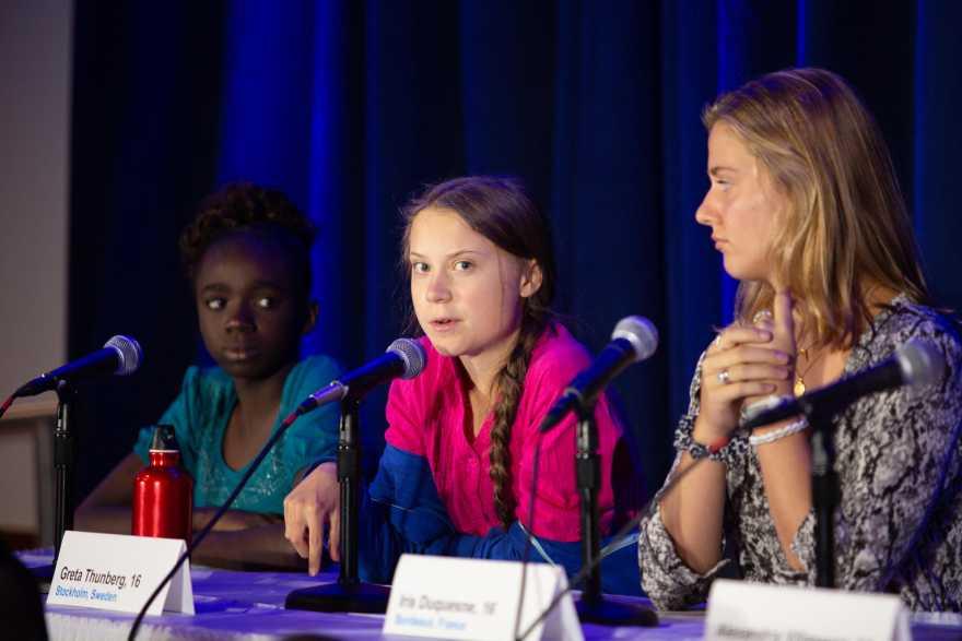 Greta Thunberg och två andra barn vid en presskonferens.