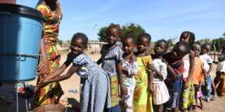 Barn som tvättar händer utanför skolan, Gbessasso, Elfenbenskusten.