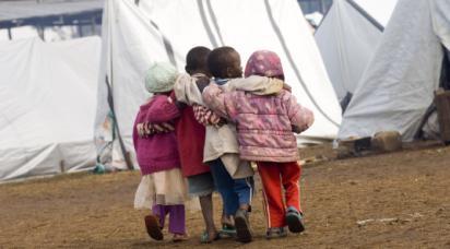 Fyra barn går och håller om varandra i ett flyktingläger.