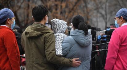 En familj med ett barn med masker för att skydda sig mot det nya coronaviruset