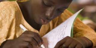 Flicka i Senegal skriver i anteckningsbok.