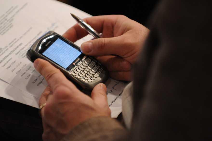 Händer som håller en mobiltelefon.